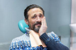Concerned man hand on cheek visits Buffalo Grove dentist
