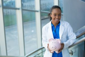 smiling dentist holding pink piggy bank