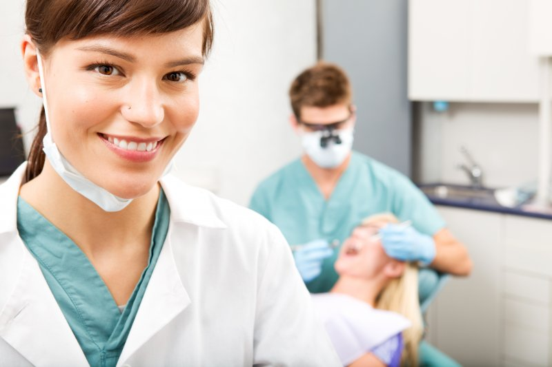 a dental assistant smiling while the dentist examines a female patient's smile in the background